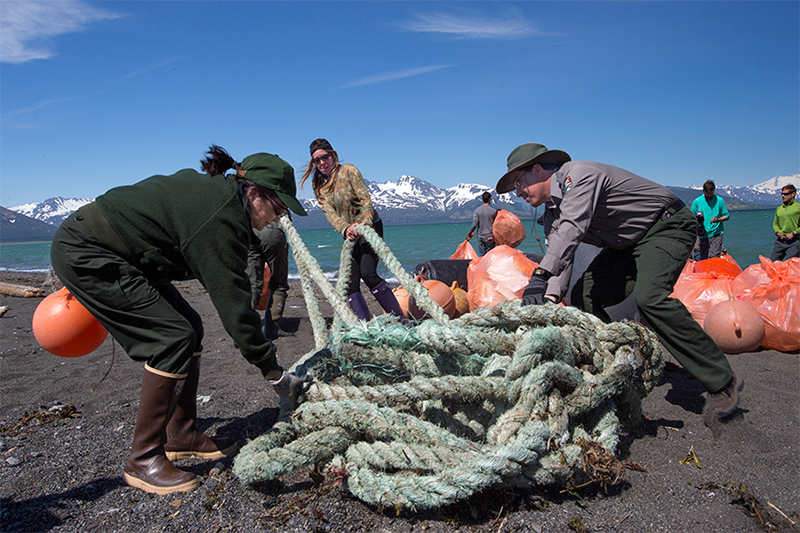 GYRE expedition participants drag trash off of Hallo Bay Beach. Much of the trash was gear from fishing boats. Photo © Kip Evans — GYRE)