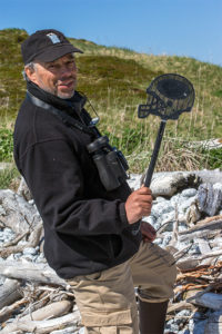 Author and marine biologist Carl Safina displays one of many football helmet-shaped fly swatters that were in the trash at Wonder Bay Beach. It was assumed that the items came from a shipping container. Photo © Kip Evans — GYRE