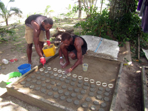 Conservation Assistants Ratu Ewasa Kuribola and Nacanieli Tavaga prepare cement discs used for propagating corals. Image © Reef Explorer Fiji, Ltd.